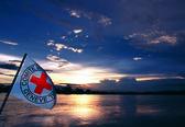 Foto: Eine Rotkreuzfahne an einem See.