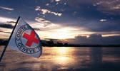 Foto: Eine Flagge des Roten Kreuzes weht vor der Weite des Horizontes. Die untergehende Sonne spiegelt sich auf der Wasseroberfläche. Dieses Foto ist gleichzeitig ein Link und führt Sie zu der Unterseite: Grundsätze.