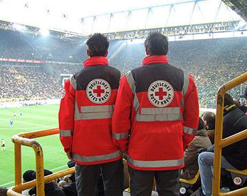 Foto: Zwei Sanitäter stehen im Fußballstadion und blicken auf das Feld.