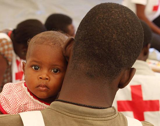 Foto: Ein haitianisches Baby schaut über die Schultern eines Rotkreuzhelfers.
